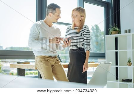 Communication at work. Positive delighted nice man looking at his colleague and smiling while having a conversation with her