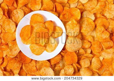 Golden Chips Potato Texture. Chips On A White Plate Standing On A Big Pile Of Chips