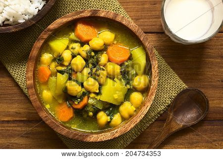 Vegan chickpea curry or chana masala with spinach potato and carrot served in wooden bowl with lassi drink photographed overhead with natural light (Selective Focus Focus on the top of the curry)