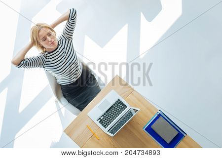 Attempt to relax. Pleasant attractive peaceful woman closing her eyes and trying to relax while being at work