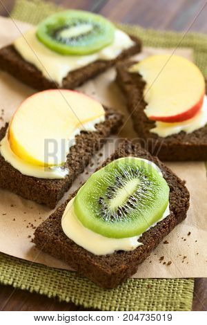 Wholegrain bread sandwiches with cream cheese and fresh apple or kiwi slices photographed with natural light (Selective Focus Focus in the middle of the kiwi slice on the first sandwich)