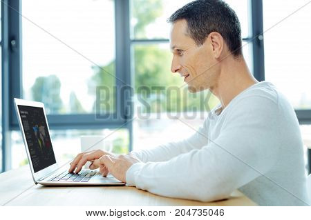 Being focused. Positive cheerful delighted man sitting in front of the laptop and working on it while being focused on his task