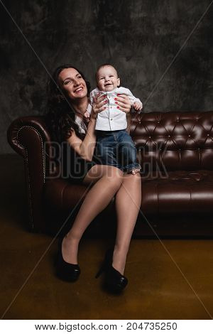 happy mother and son sitting on sofa