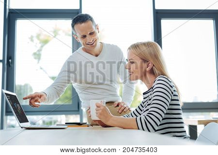 Business statistics. Cheerful positive blonde woman holding her cup of tea and smiling while looking at the world map