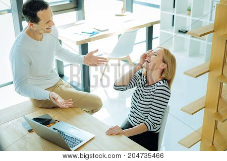 Positive emotions. Cheerful beautiful positive woman looking at her colleague and laughing while listening to his jokes