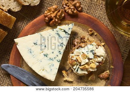 Blue cheese and walnut canape on plate with beverage on the side photographed overhead with natural light (Selective Focus Focus on the top of the canape and the blue cheese slice)