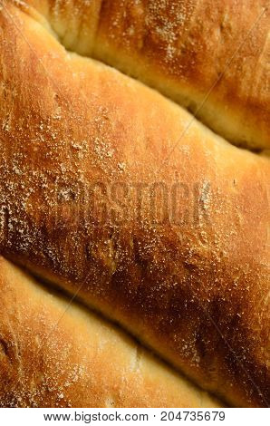 Close up (macro) of the golden brown crust of a freshly baked loaf of white bread.