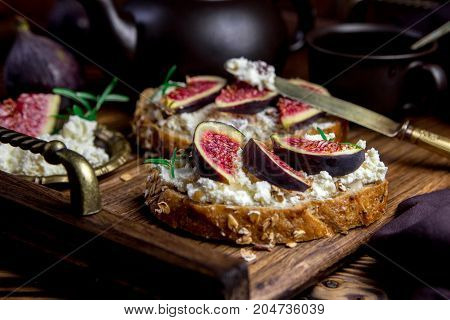 toast with cottage cheese and figs on a wooden tray