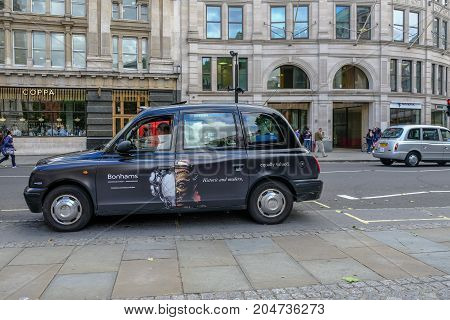 London UK - August 3 2017: London black cab parked at the side of the road waiting for a passenger. Daytime shot of a street scene.