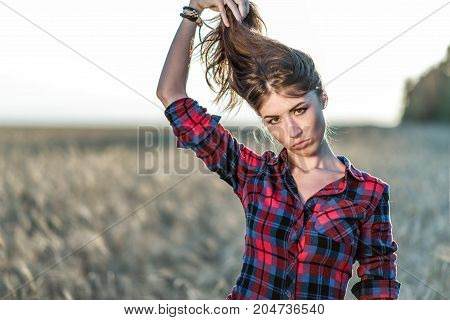 Beautiful girl in the field. Summer in nature. Happy holds her hair. In the evening shirt a brunette woman, close-up portrait. Fun playing with the hair, a concept of fun.