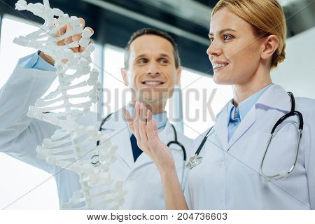 DNA studies. Beautiful nice female scientist standing together with her colleague and smiling while studying DNA