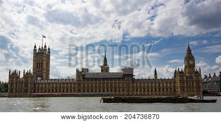 Full side view of the Houses of Parliament with boat in front on the River Thames on a beautiful clouded day in London.