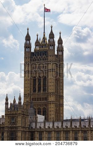 Close Up Vertical shot of the Victoria Tower or the King's tower of the Palace of Westminster and Houses of Parliament with the British flag waving in a cloudy sky.