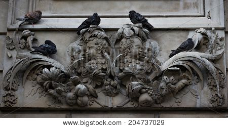 Outdoor sculptural facade of St. Paul's Cathedral in London England with pigeons resting on it.