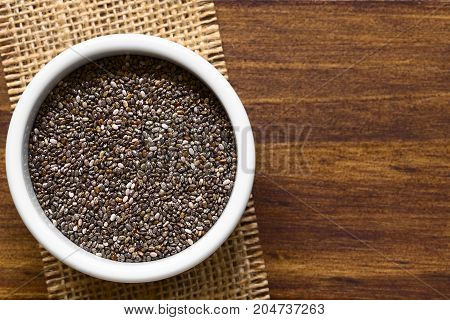 Healthy chia seeds (lat. Salvia hispanica) in small bowl photographed overhead with natural light (Selective Focus Focus on the top of the chia seeds)