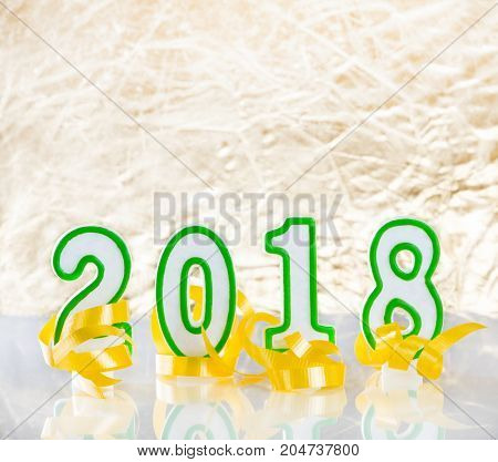 2018 New Year numbers and yellow ribbons on bright golden background