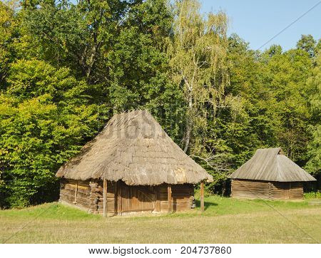 old wooden houses with a thatched roof in the autumn at the National Museum of Architecture in Pirogovo where there is a collection of ancient wooden houses and temples near Kiev Ukraine