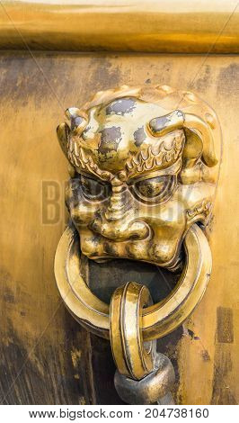 Beijing, China - Oct 30, 2016: Cloesup of ornate bronze lionhead handle on water urn at the Entrance to the Gate of Heavenly Purity, or Celestial Purity (Qianqingmen). Forbidden City (Gu Gong, Palace Museum).