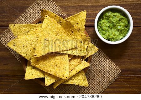 Corn tortilla chips in bowl with avocado dip on the side photographed overhead on wood with natural light (Selective Focus Focus on the top of the tortilla chips)