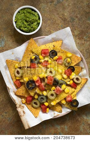 Baked nachos with cheese green and black olives tomato and corn with guacamole on the side photographed overhead on slate with natural light