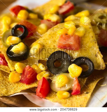 Baked nachos with cheese green and black olives tomato and corn photographed with natural light (Selective Focus Focus on the front of the tortilla chip in the middle)