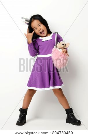 Happy young little asian child girl ready for birthday with little dog in bag smiling laughing on white background