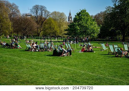London, England, April 2017: People relax in London St James Park with Big Ben seen in background England