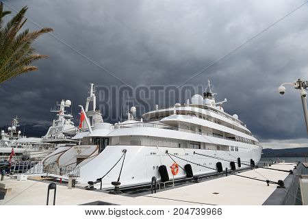 july 2017 Montenegro. Luxury yacht at the pier of the marina in Porto Montenegro with cloudy dark sky