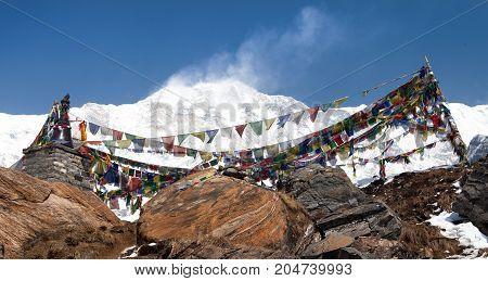 Buddhist prayer flags and Mount Annapurna from Annapurna base camp Himalaya Nepal
