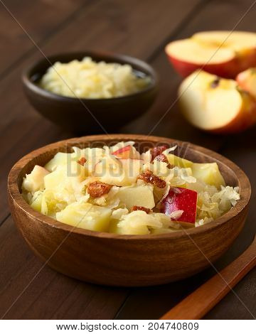 Potato sauerkraut and apple salad with fried bacon served in wooden bowl photographed with natural light (Selective Focus Focus in the middle of the salad)