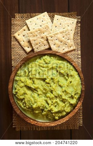 Green pea and parsley dip or spread in wooden bowl with soda crackers photographed overhead with natural light (Selective Focus Focus on the top of the dip)