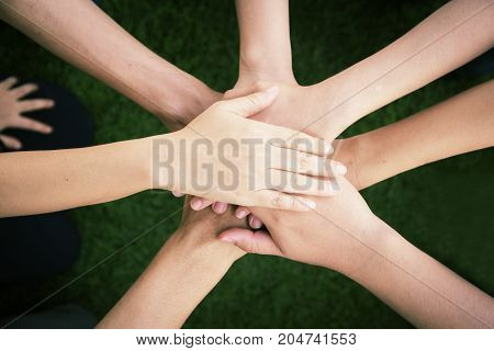 Close up top view of young people putting their hands together. Friends with stack of hands showing unity and teamwork.