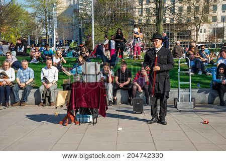 London, England, April 2017: People watch show of one of the street performers near Jubilee gardens and London Eye England