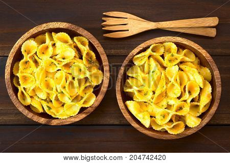 Pasta with pumpkin and parsley sauce served in wooden bowls photographed overhead on dark wood with natural light (Selective Focus Focus on the top of the dish)