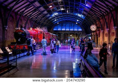 London, England, April 2017: Visitors at platform 9 3/4 and Hogwarts Express in Warner Brothers Harry Potter Studio Tour London