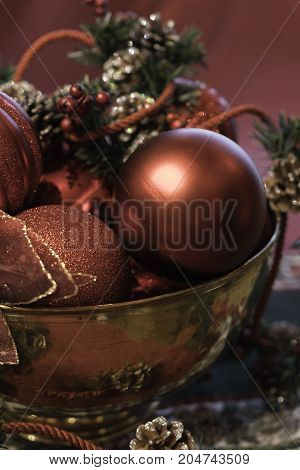 close up vertical of Christmas ornament display in brass bowl