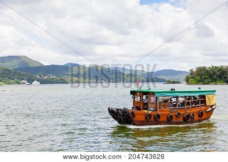 HONG KONG - JULY 14 2017: A converted fishing trawler carries passengers to outlying islands in the Sai Kung peninsula. The village of Sai Kung is also noted locally for its seafood restaurants and floating fish market.