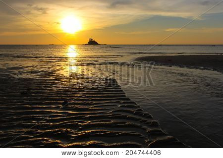 Beautiful sea sunset with small island silhouette on the beach & rippled sand on the beach during Low tide.Natural wave pattern in sand on a beach texture.Tropical beach style background for add text.