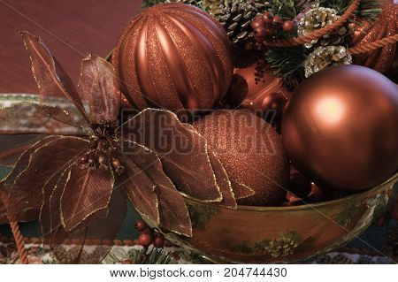 close up horizontal Christmas decoration display of a brass bowl filled with shiny red ball ornaments, pine cones, and a poinsettia flower