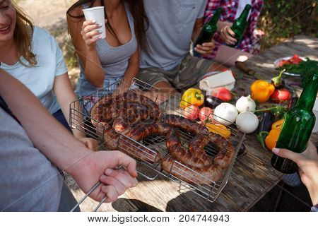 The man brought a large appetizing sausage, fried at the stake. Friends rest on nature and fry meat. Summer outdoor recreation with the best friends. Healthy lifestyle, fresh summer vegetables.
