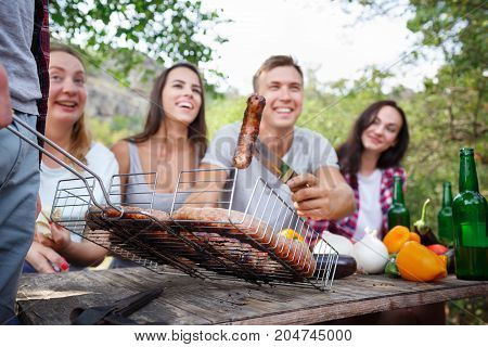 Romantic picnic. Group adult friends enjoying a healthy outdoor meal sitting together at a table in a lush green garden laughing and joking. Friends Outdoors Nature Picnic Chilling Out Unity Concept.