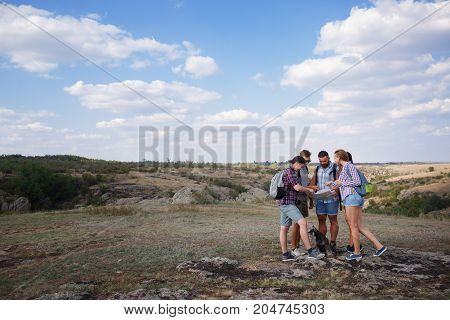 Group of Friends. Traveler Looking on the Map and Plan to Trekking and Adventure in the Forest - Travel in Holiday Summer Concept. Friends took a dog on a summer hike and look at the map.