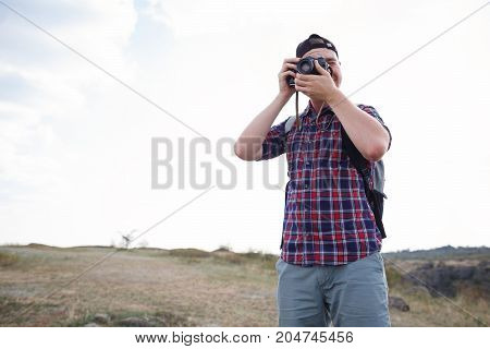 Man Traveler with photo camera and backpack hiking outdoor Travel Lifestyle survival concept mountains clouds on background. The best time to travel to the mountains. Traveler in the mountains.