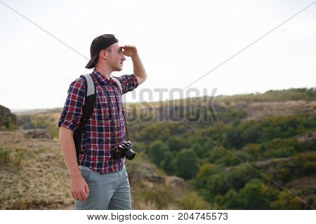 The guy looks into the distance, standing on the mountain. Beautiful mountain view on the background. Man in search of a way. Summer trip through the mountains without a map. Summer time.