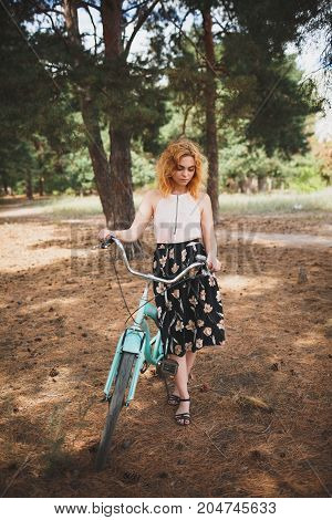 Summer walk in the forest with a beautiful blue bike. Active woman riding bike bicycle in fall autumn park. Healthy lifestyle and recreation leisure activity. Beautiful girl in the forest in autumn.