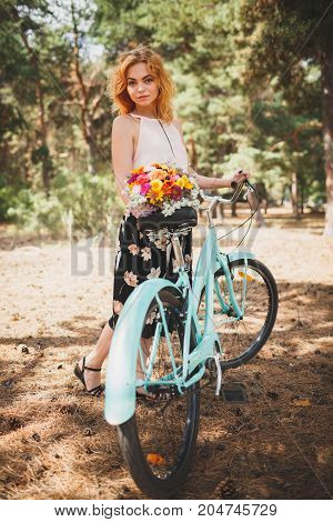 Lovely girl with autumn flowers on a walk in the woods. A young red-haired girl in a beautiful forest is resting from the city bustle. Woman with flowers in the background of a coniferous forest.