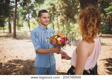 Young man giving his girlfriend a flowers and kissing celebrating valentines day. Young couple in love outdoor.Stunning sensual outdoor portrait of young stylish fashion couple posing in park.