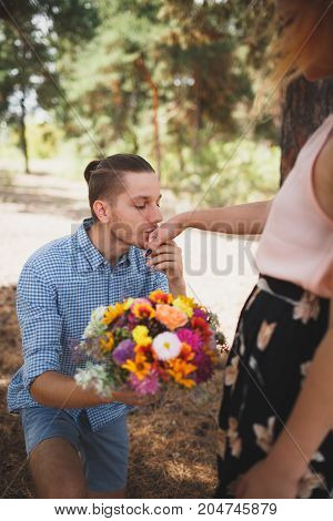 Beautiful flowers were presented to the girl for the holiday. A young guy gives flowers to his girlfriend in the woods. Woman in a dress with a bicycle in the forest. Happy Valentine's Day.
