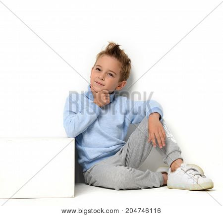 Happy young boy sitting in blue sweater thinking and looking up positive attitude on white background
