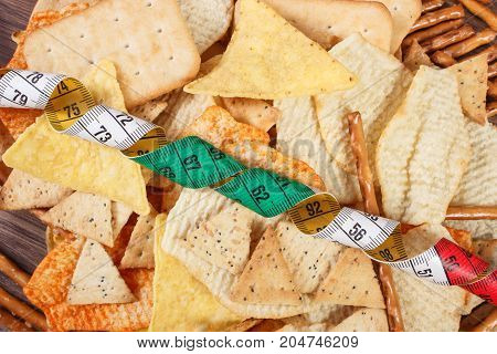 Tape Measure With Salted Crisps, Cookies And Breadsticks, Concept Of Unhealthy Food And Slimming